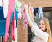 girl hanging clothes to dry on clothesline
