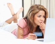 Happy lady woman holding a credit card and working on laptop